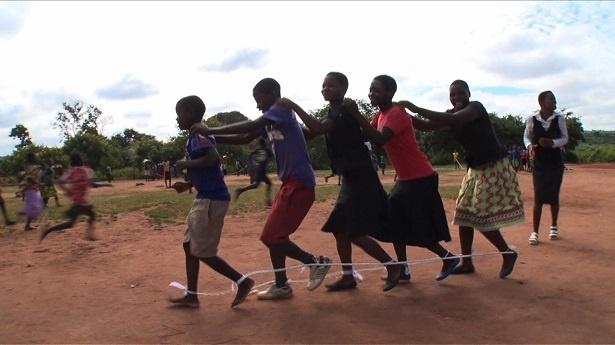 マラウイの子供たちは「ムカデ競争」の練習に笑顔