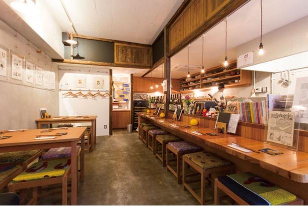 吊り下げ照明、木目調で温かみのある「町屋 あかりや」店内。入口の扉にはステンドグラスがあしらわれている