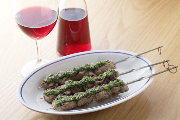 「mon an ETHNIC」の「ラム肉串のサルサヴェルデ」(3本1150円)。ワインはカラフェで楽しむスタイルを提案(1800円・300cc)