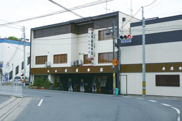 【写真を見る】曲がり松商店街のほぼ中央に位置。店舗前の大カーブを大洗女子学園・みほたちの戦車が駆け抜けた