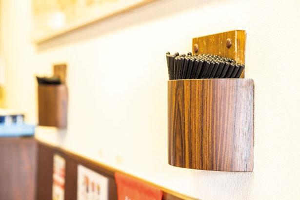 """""""忙しくて空席を待ちきれない人たちが、すぐに箸を取れるように""""という壁にかかった箸入れも1号店限定"""