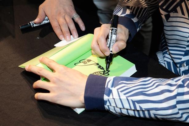ファンの目の前で1冊ずつ丁寧にサインを入れる