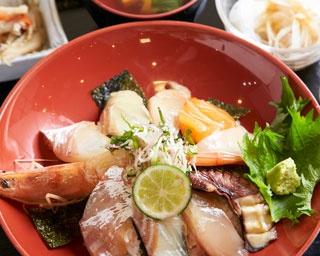 海鮮づけ丼¥1,300。中央の有頭エビが目をひく丼は、醤油に卵を加えた漬けダレに浸すことによりまろやかに。約6種のネタは日替りで小鉢3種に汁物付き