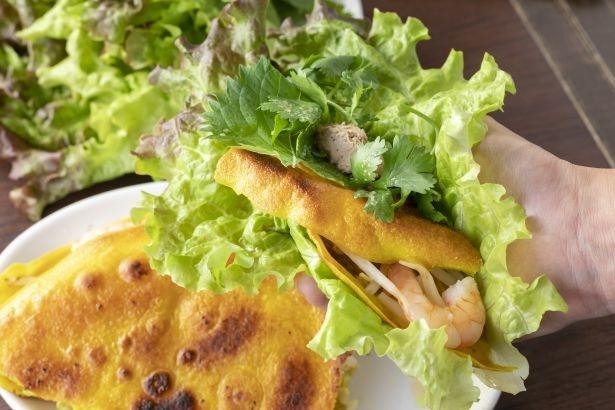 「バインセオ〜ベトナム風お好み焼き」はカットして、レバーペーストと一緒にレタスや大葉で包んで食べる。お好みでヌクチャムをかけると、ピリッとした酸味がアクセントに
