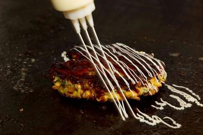 【写真を見る】鉄板で焼かれた定番メニューの豚玉(918円)は、キャベツに対して小麦粉の使用を最小限に抑えて軽めの仕上がりにしている