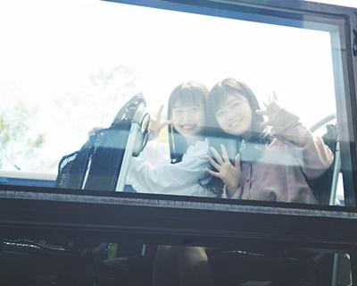 バスの窓から、いってきまーす!と手をふる2人