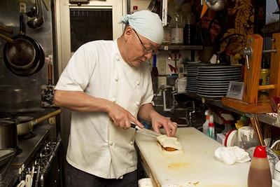 【写真を見る】「特注のソースと生パン粉にこだわっています」という名物のカツサンドを手際よくつくる中尾さん。カツサンドはディナータイムのみ提供し、テイクアウトも可