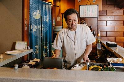 【写真を見る】ステーキ屋で働いていた髙橋さんが「天ぷらと串 髙尾」を継いで30年。「髙尾という店名は、親族の名字の『髙橋』と『尾崎』から一文字ずつ取ったんですよ(笑)」