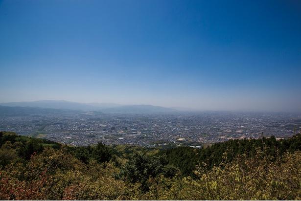 【写真を見る】四王寺山 / 展望台では視界いっぱいに市街地が広がり、遠くに脊振山が見える