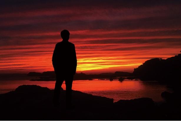波の静かな海に真っ赤に染まった夕日が沈む。絶景を独り占めできる贅沢な時間だ