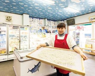 若女将が持つのは、最上級チリメンジャコ。直売所には、地元で捕れたワカメやエビなどの加工品が並ぶ。期間限定の珍しいものも多い