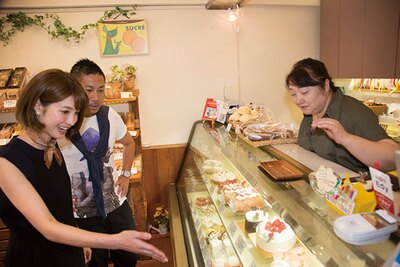パンや焼き菓子も並んだ店内で、店主の佐藤さんにオススメを聞く2人
