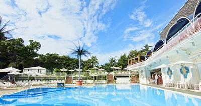 白い造りのプールサイドを囲む緑は、ホテルの名物である日本庭園の木々