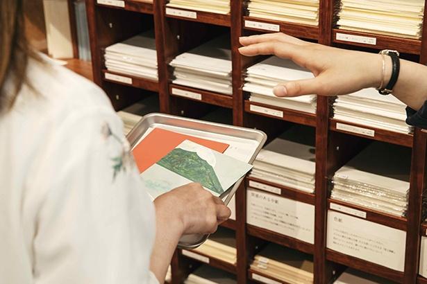 【写真を見る】壁際の棚にはレザーや布製など60種以上の表紙の素材がずらり。表と裏で別の素材を選ぶこともできる。今後は男性向けに無地のものも増える予定