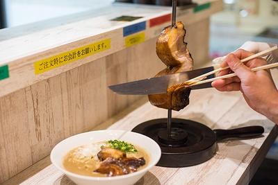 煮豚(1枚)以外のポルコ(4枚)はラーメンと別で提供。本場のスタイルと同様に、客の目の前で切り分けてくれる