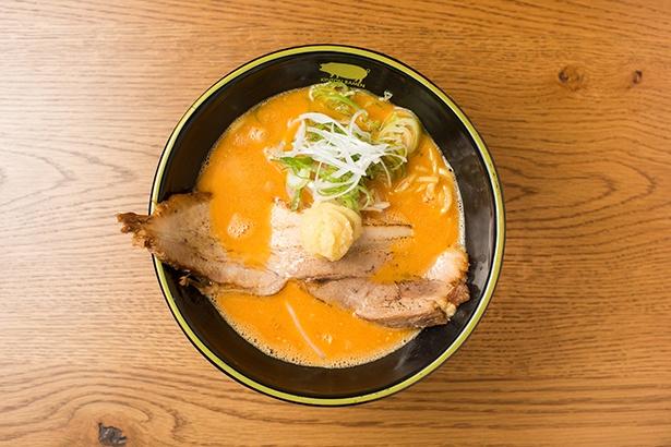 【写真を見る】「豚骨 スパイシーガーリック」(950円)。クリーミーな豚骨100%スープに特製辛味噌ダレを合わせ、おろしニンニクをトッピング