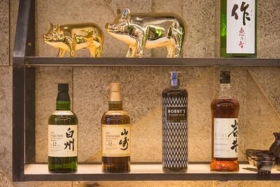【写真を見る】バーカウンターの奥の棚には酒瓶がズラリ。「白州」や「山崎」などウイスキーは日本のものを各種取りそろえている
