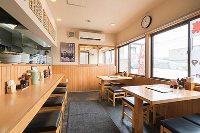 入口から見て右側にカウンター席とテーブル席を配置。奥には製麺室が見える