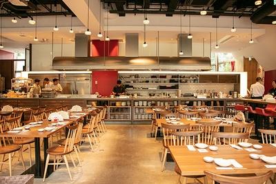 広い店内を横断するオープンキッチンが備えられた「GYOZA IT.」。特注の鉄板は1度に76人前の餃子が作れる