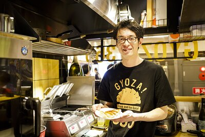 「GYOZA! 365」のオリジナルTシャツを着た荒木拓善店長。イタリアンシェフと一緒にレシピを製作しているそう