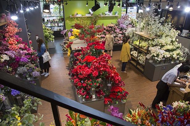 【写真を見る】色・種類別にたくさんの造花が並べられた1階フロア
