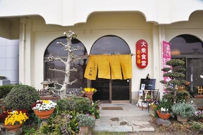 黄色い暖簾(のれん)が目印で、店先にはきれいに花や植物がディスプレーされている。店前に駐車場あり