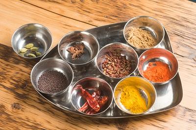 「花山椒のポークキーマカレー」には8種のスパイスを配合。手前右から時計回りにターメリック、赤唐辛子、マスタードシード、カルダモン、八角、花山椒など