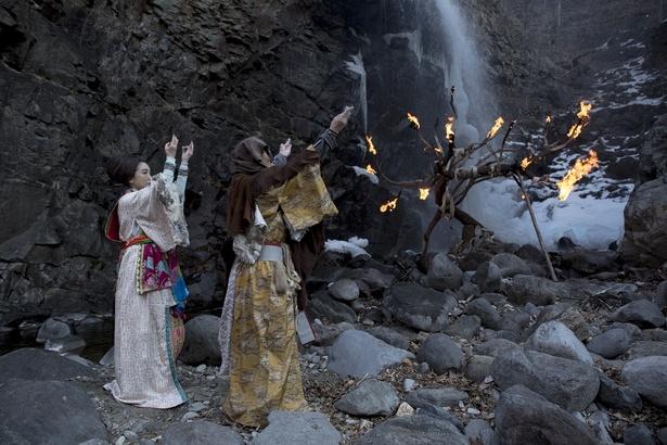 木に灯る火へ向けて両手を掲げる男女の意味するものは…