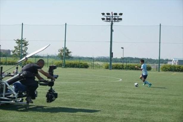 真剣なプレーの撮影。合間にはスタッフとボールを蹴り合うリラックスシーンも