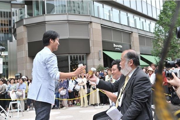 会場に集まった記者に商品を配る桐谷健太