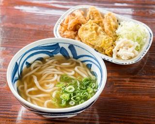 お代わり自由の惣菜が付いた「温うどん」(550円)。中太麺は博多のうどん寄りでやや柔め。スープはダシ昆布やアゴ、削り節、花がつおを使い、薄めの味付けに仕上げる