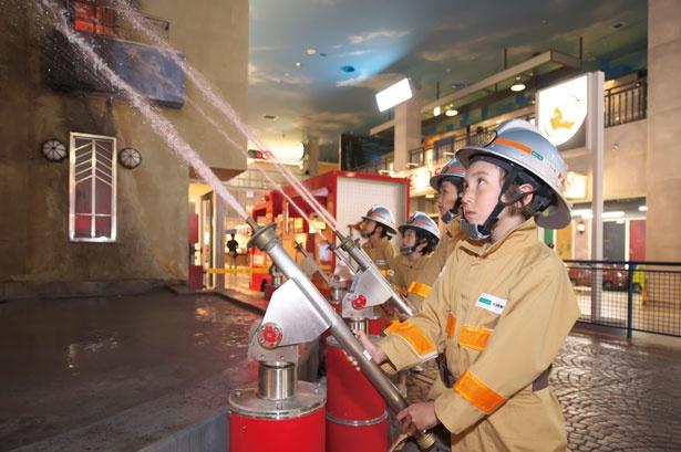 火災現場に着いたら、放水開始。火を狙って、放水銃の角度を定めて!/キッザニア甲子園