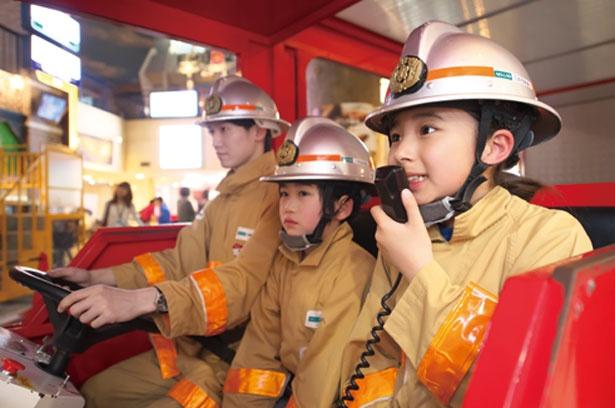 火災現場に向かう消防車の中で「消防車が通ります」とアナウンス。街の安全を守る任務に身が引き締まる/キッザニア甲子園