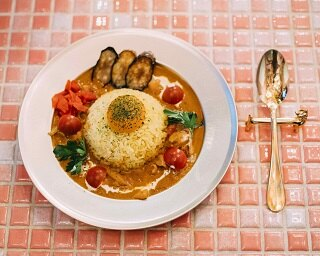 看板メニューの「宮殿カリー」(800円)。ナスとフレッシュトマトをトッピングし、卵黄でまろやかな口当たり