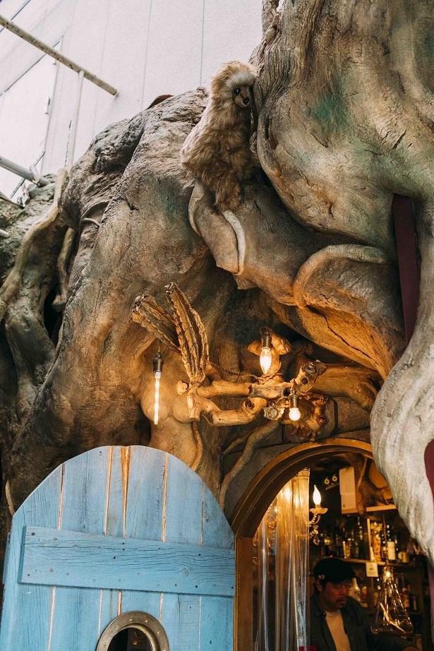 【写真を見る】擬木で覆われた入り口。大きな木に覆われた洞窟の中に一歩足を踏み入れると、異空間が広がる