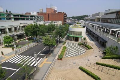 【写真を見る】緑豊かなショッピングモール。緩やかな坂道に沿って建てられている