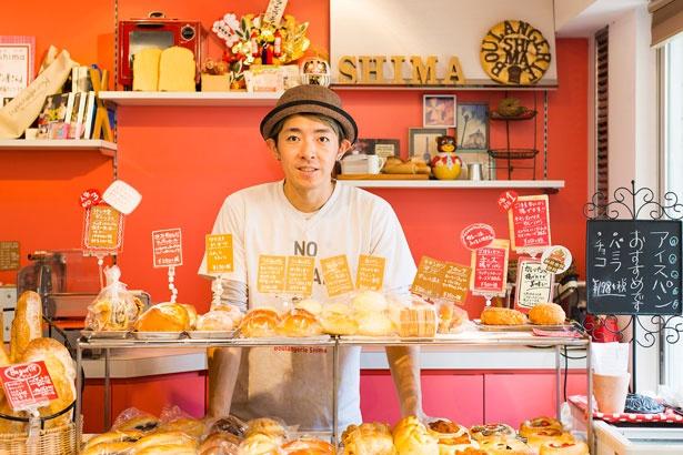 島 健太店主。店内には多種多様なパンがズラリと並ぶ