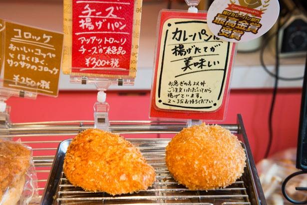 【写真を見る】「チキンスパイスカレーパン」(右、270円)と、同様の生地で揚げる「チーズ揚げパン」(左、324円)。どちらも注文してすぐに揚がるよう工夫が施されている