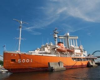 【写真を見る】全長100mに及ぶ大きなオレンジ色の船体が目を引く