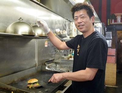 ジューシーな牛肩肉100%の極厚粗挽きパティを焼く、店長の天野義 嗣さん/ドラゴンバーガー