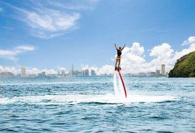 「AQUA TAIL」のフライボード体験 / 水上バイクの船尾に、ボードに固定されたブーツが取り付けられ、足元から海水を噴射し空を飛ぶ。出力は水上バイク側で行う