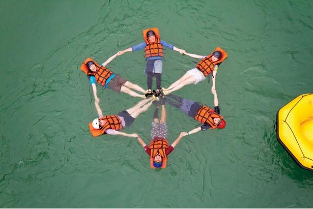 「メインストリーム」のラフティング体験 / 球磨川でみんなで手をつないで花のアーチを作る。コース途中の橋の上か、ボートの上に立って撮影してもらうときれいに撮れる