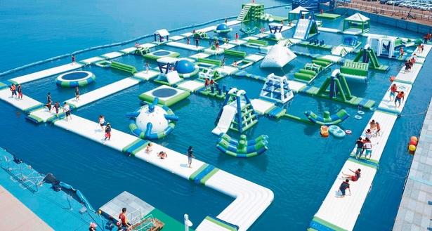 トランポリンやジャングルジムなどのエア遊具が組み合わさり、巨大迷路のように構成された海上アスレチック。落ちればぬれてしまう、海上のスリル がたまらない!(利用制限:10歳以上)