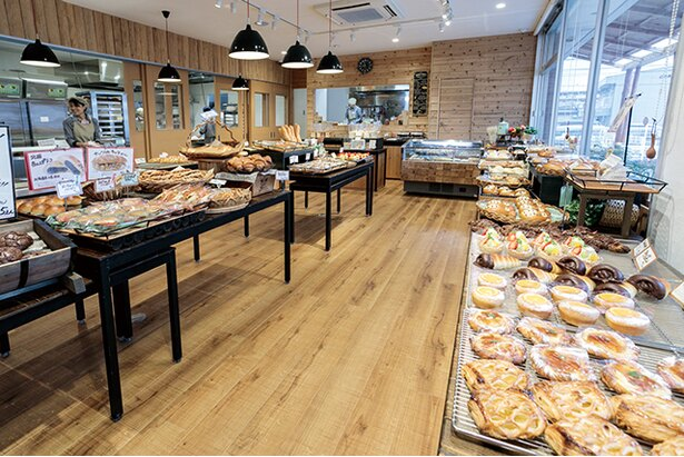「小麦工房 Panaché 三苫店」の無垢の木を多用した温かみのある店内は、パンを作る様子が見え臨場感がある。イートインは室内とテラス席があり