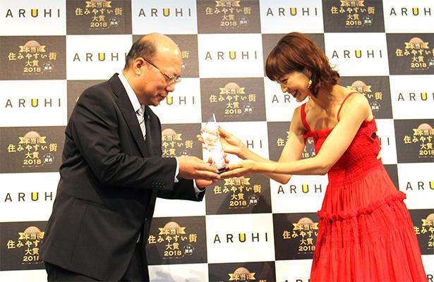 大賞を獲得した尼崎代表の樋上氏に、安田からトロフィーが授与された