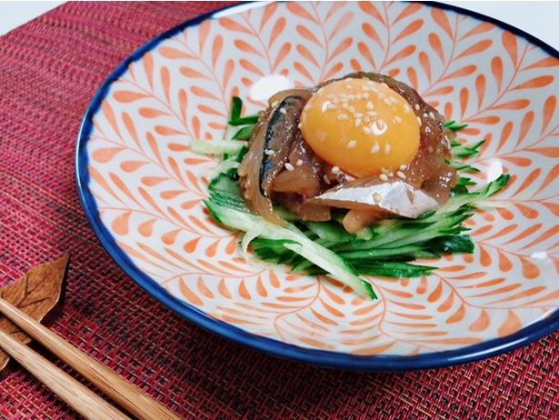 【写真を見る】オカマリ流「ピリ辛アジユッケ」。タタキにして焼き肉のタレで揉み、卵黄を落とすだけ。辛口ダレを使えばピリ辛な感じでご飯が進み、さらに七味を足しても美味しかった