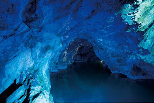 【写真を見る】「稲積水中鍾乳洞」の「青い回廊」。ブルーの照明を使った幻想的な演出で観光客を迎える
