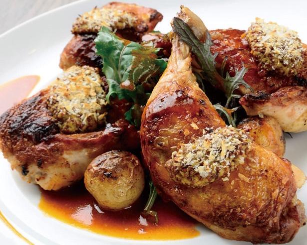 【写真を見る】ikariyaベーシックコースで登場する名物料理丸鶏コンフィは、ワインと共に味わいたい一品/イカリヤ食堂