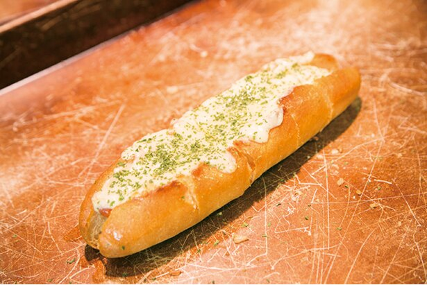 「パン・ド・クルール 照葉スパリゾート店」。店の住所から命名した「5丁目ドッグ」(小302円、大450円)。チョリソーととろ~りチーズでやみつきに