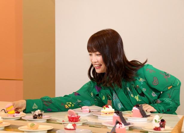 【写真を見る】お目当てのスイーツを見つけた川栄李奈は、他に客はいないのに我慢できず、離れた所まで手を伸ばしてしまう